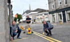 Mark (left) and Norman Esslemont (right) of Esslemonts measure the width of the pavement in Thistle Street, as Rob Goldie of Baskin-Robbins looks on. Picture by DARRELL BENNS
