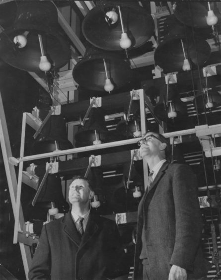 Michael Howard whose firm cast Aberdeen's St Nicholas Bells and Mr Robert Leys, the carilloneur, study them with an expert eye. The bells with two clappers can be rung either by hand or electrically. 1965.
