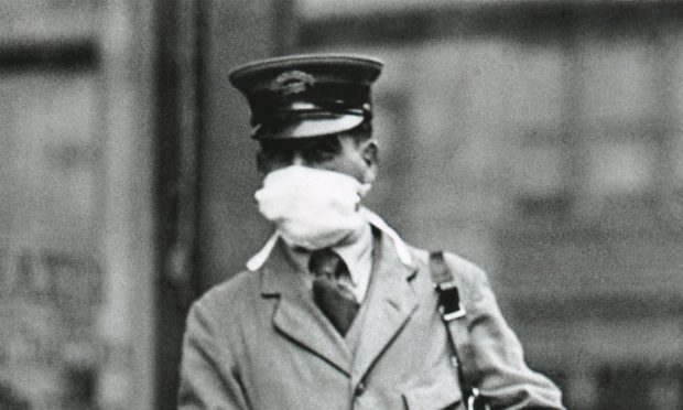 A letter carrier in New York City wearing a gauze mask to avoid catching influenza. in 1918.