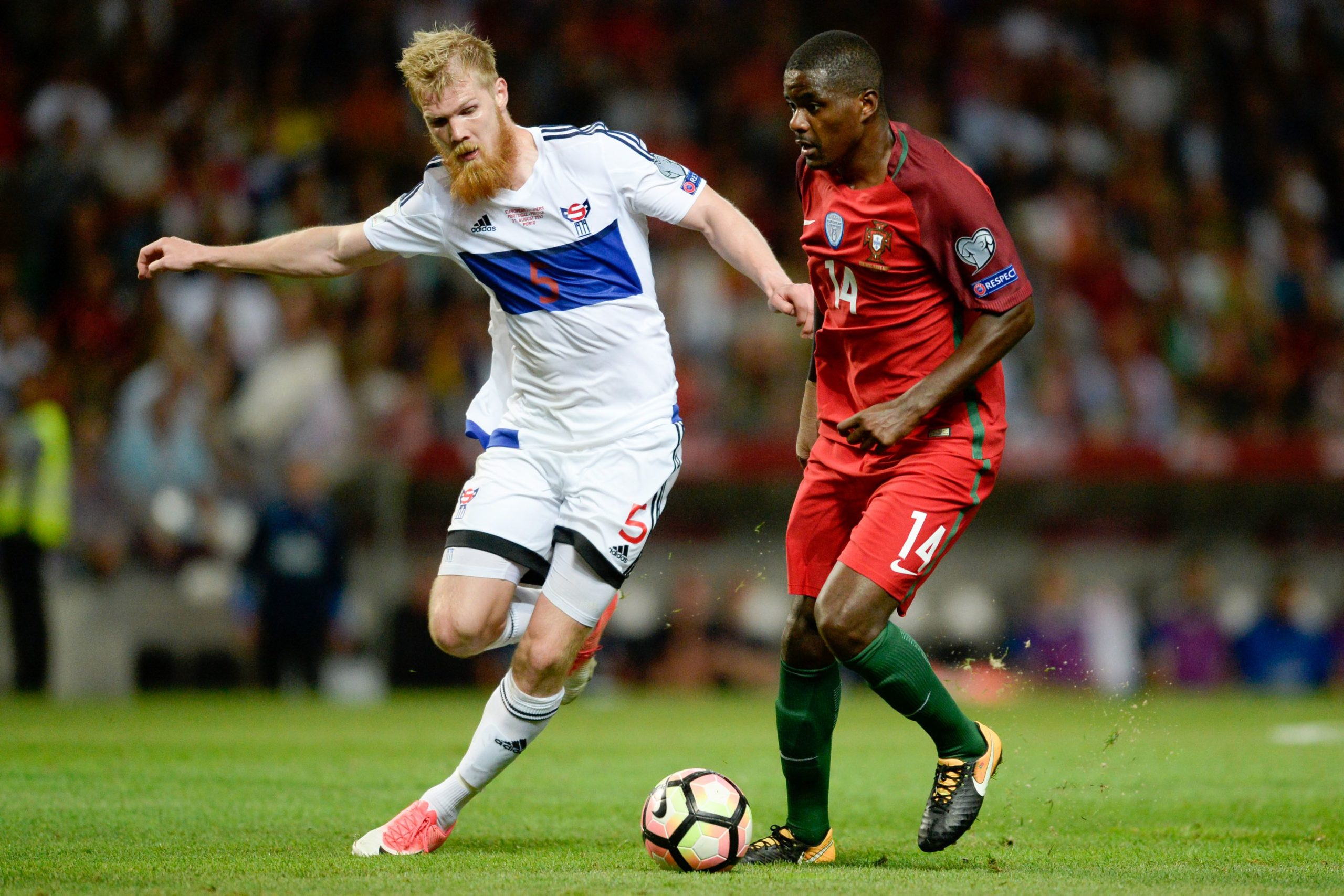 Portugal's William Carvalho fights for the ball with Odmar Faero of Faroe Islands during a World Cup qualifier in Porto.