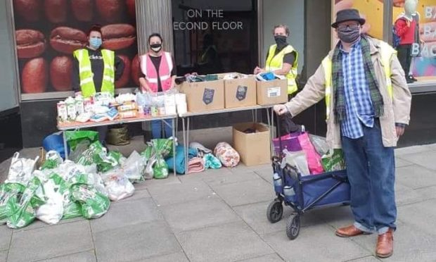 Justin Ritchie (right) and the Street Friends Helping The Homeless volunteers at their table in St Nicholas Street, outside Marks And Spencer.