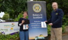 Jennie Devlin, of Highland Hospice, receiving the tablets from president of RCILN Bryan Smith