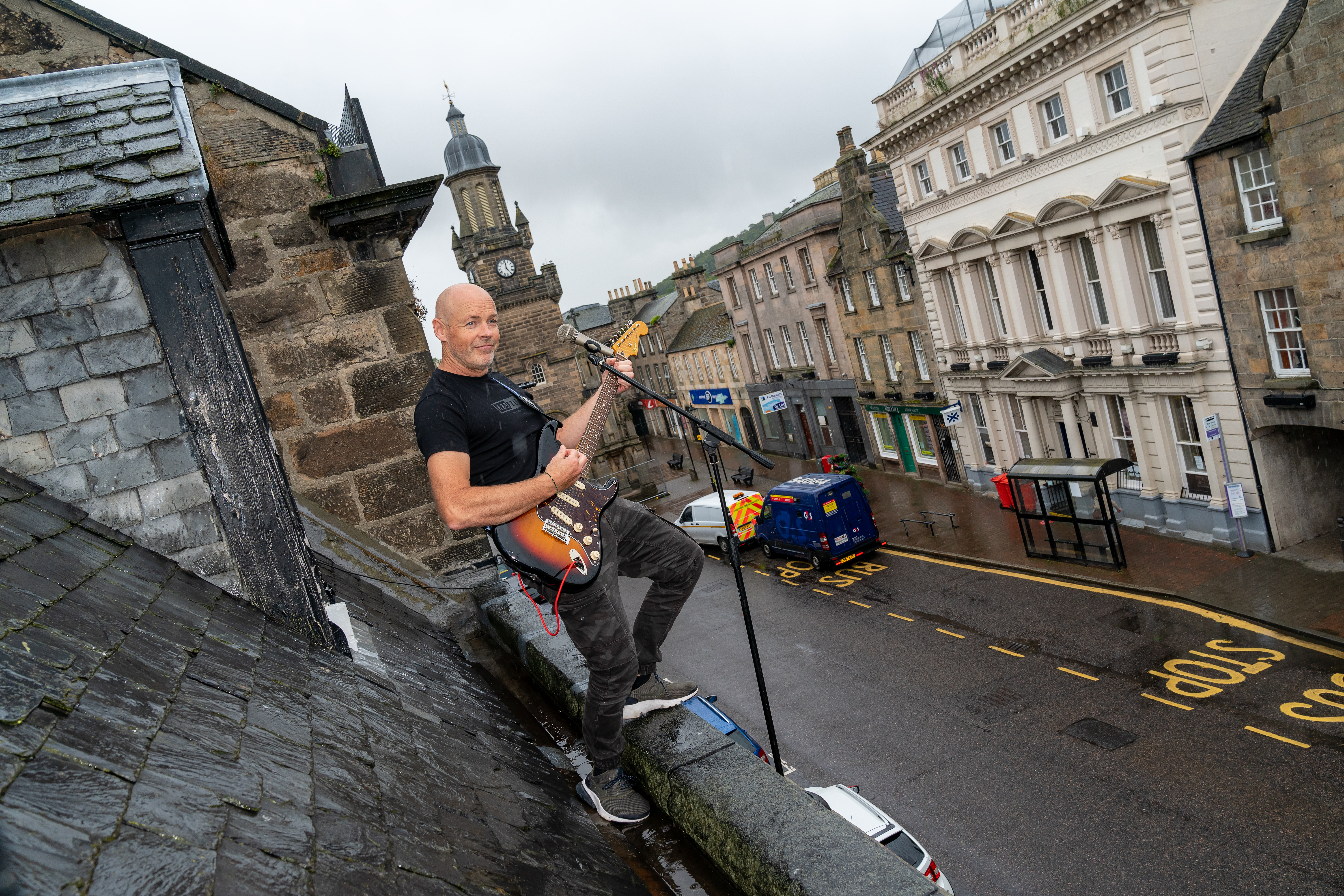 Dave Levon singing from his rooftop on High Street, Forres.