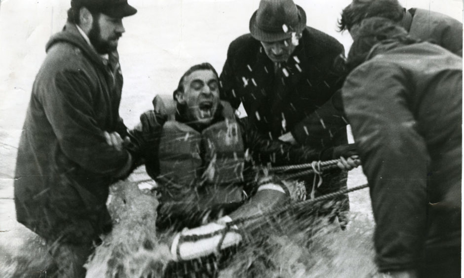 """A crew member of the Polish trawler """"Nurzec"""" screams in agony because of the freezing water as rescuers wade in to remove him from the Breeches Buoy off the Aberdeen coast."""