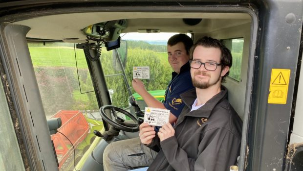 Ewan (in blue) and Ross MacIver with the SSEN farm safety stickers.