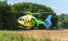 Scotland's Charity Air Ambulance taking off beside Bridge of Alvah, where two men were injured.
