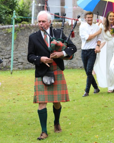 Mrs Macgowan's father playing the bagpipes.