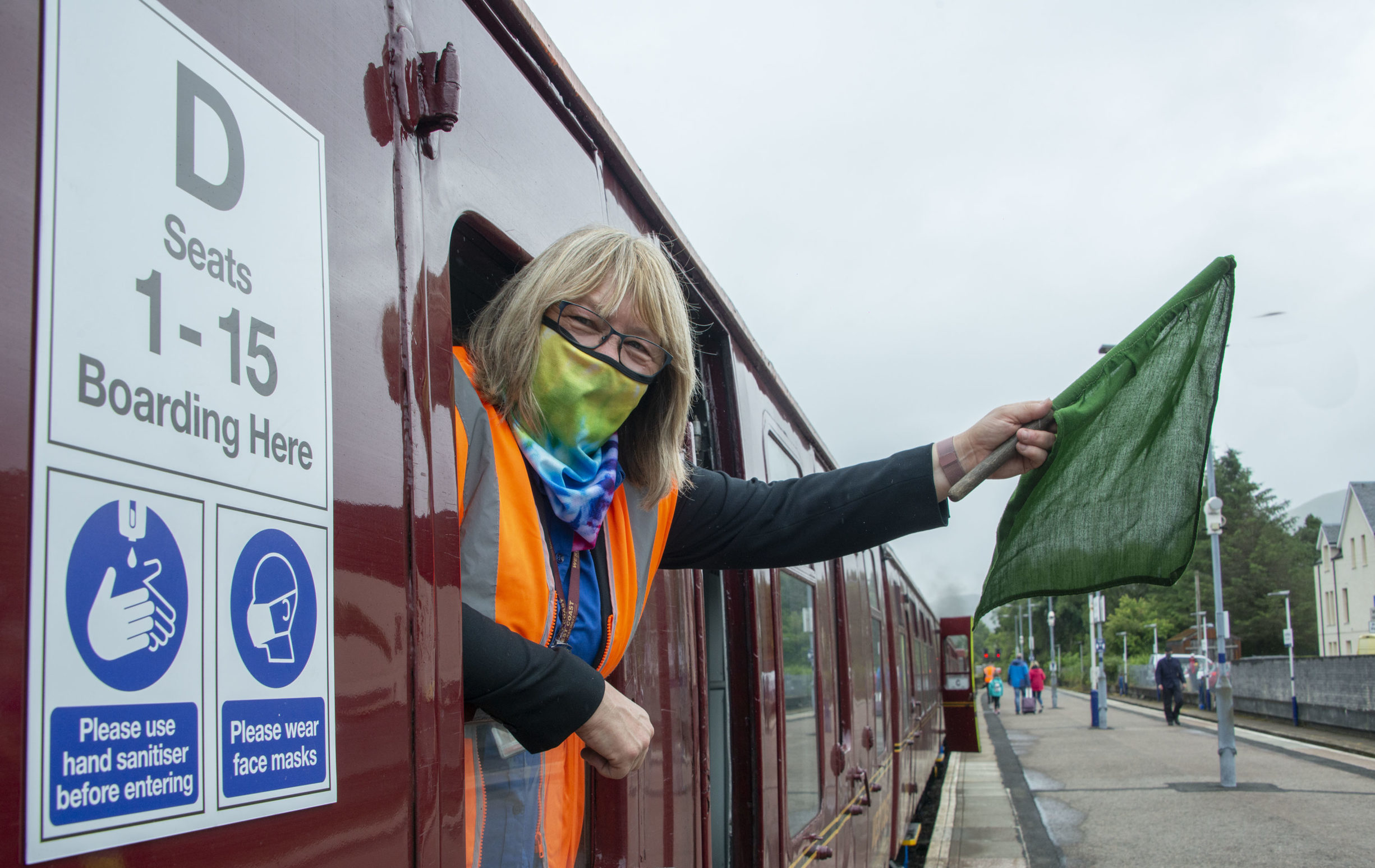 Jacobite steam train Manager, Florence MacLean waves off the train at the delayed start of the new season