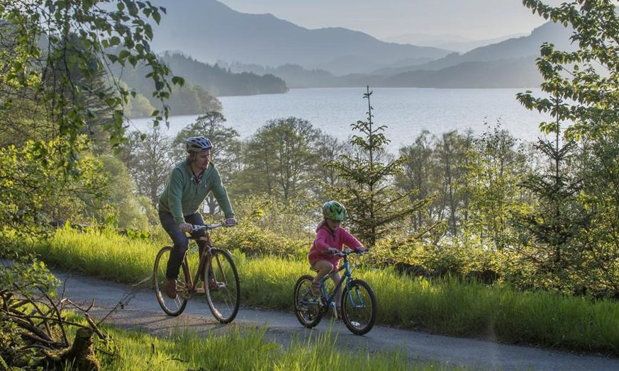 A family enjoying the stunning scenery along the banks of Loch Venachar on National Cycle Network Route 7. As part of the Aberfoyle-Callander and Lochs and Glens North portion of NCN 7, this stretch is notable for breathtaking views across the Loch and rolling mountain forests above.
