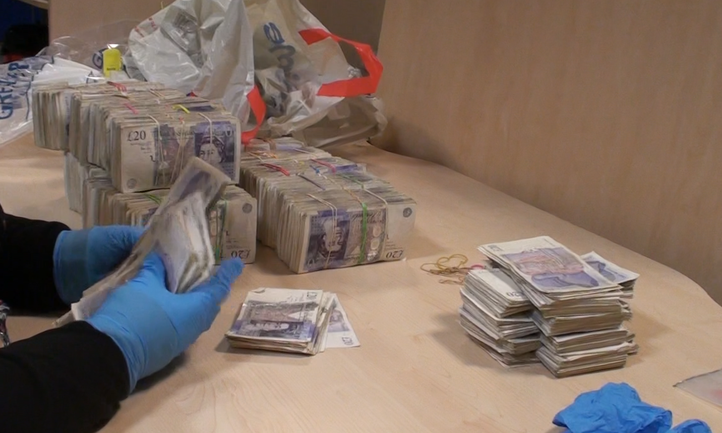 A National Crime Agency officer counts some of the confiscated cash.