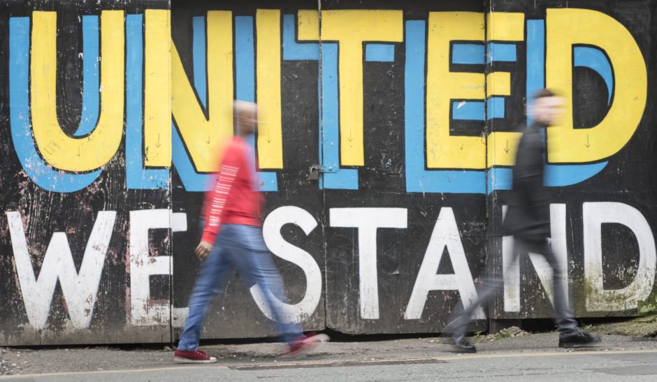 A general view of people walking past graffiti in Leeds.