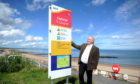 Councillor Dell Henricksen with one of the new safety signs at Aberdeen beach.