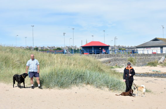 Councillor Brian Topping, with dog, Bruno, and Leona Massie with dogs Reegan and Loki, at Fraserburgh Beach.  Picture by DARRELL BENNS   CR0022642