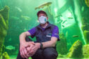Aquarist, Frazer Mackay is pictured with a reusable facemask at the aquarium.