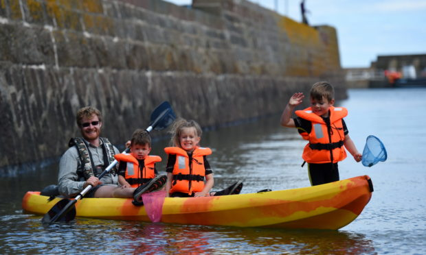 The Bottomley  family  'crabbing' from their canoe in Stonehaven harbour   Picture by Paul Glendell