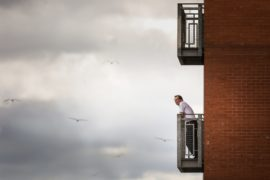 A man stands on his balcony at the City Quay, Dundee, to get some fresh air. Picture by Mhairi Edwards