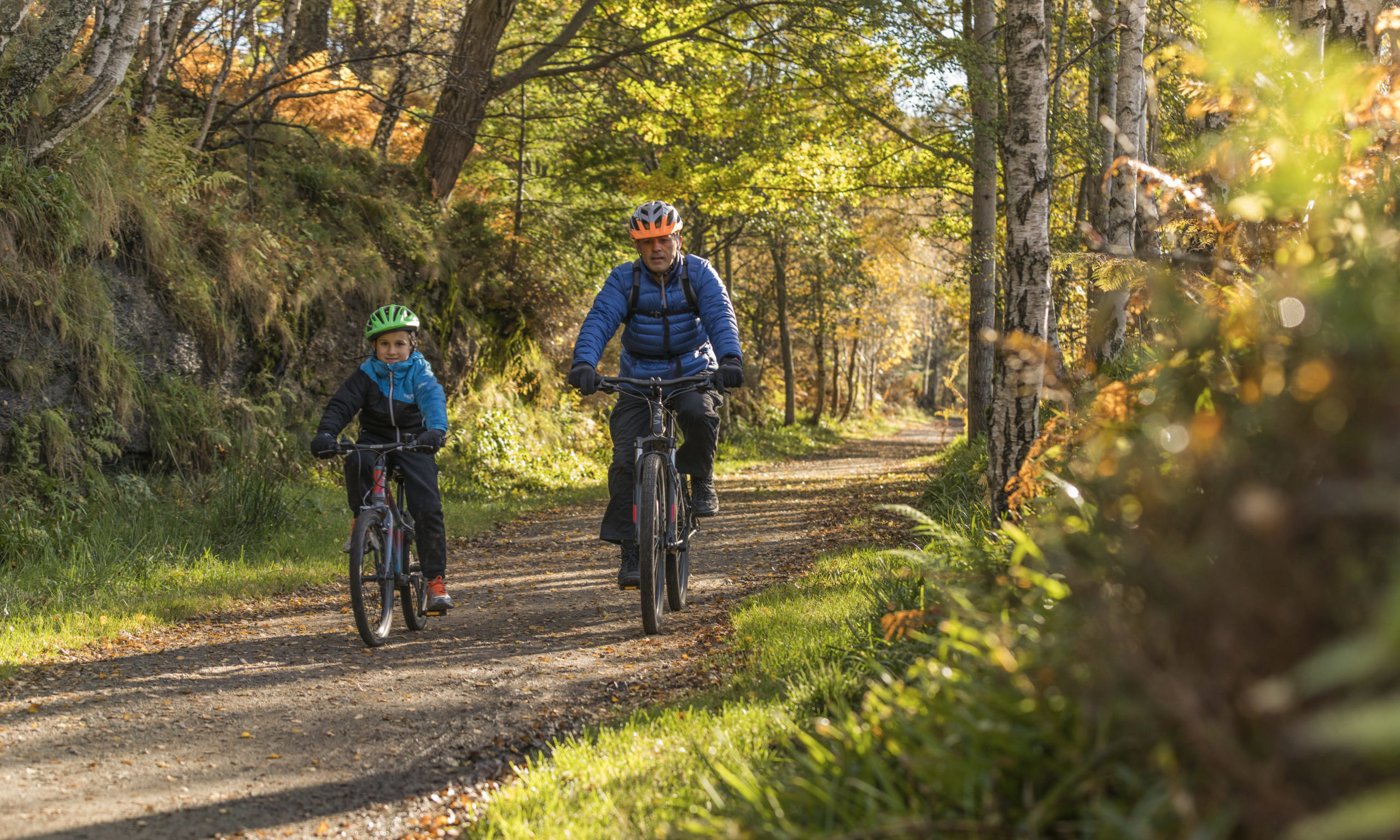 A father and son cycling a country path, Ballater. The Cairngorms National Park