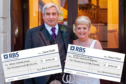 Ken Snape and Lorna Snape on their wedding day with the charity cheques.