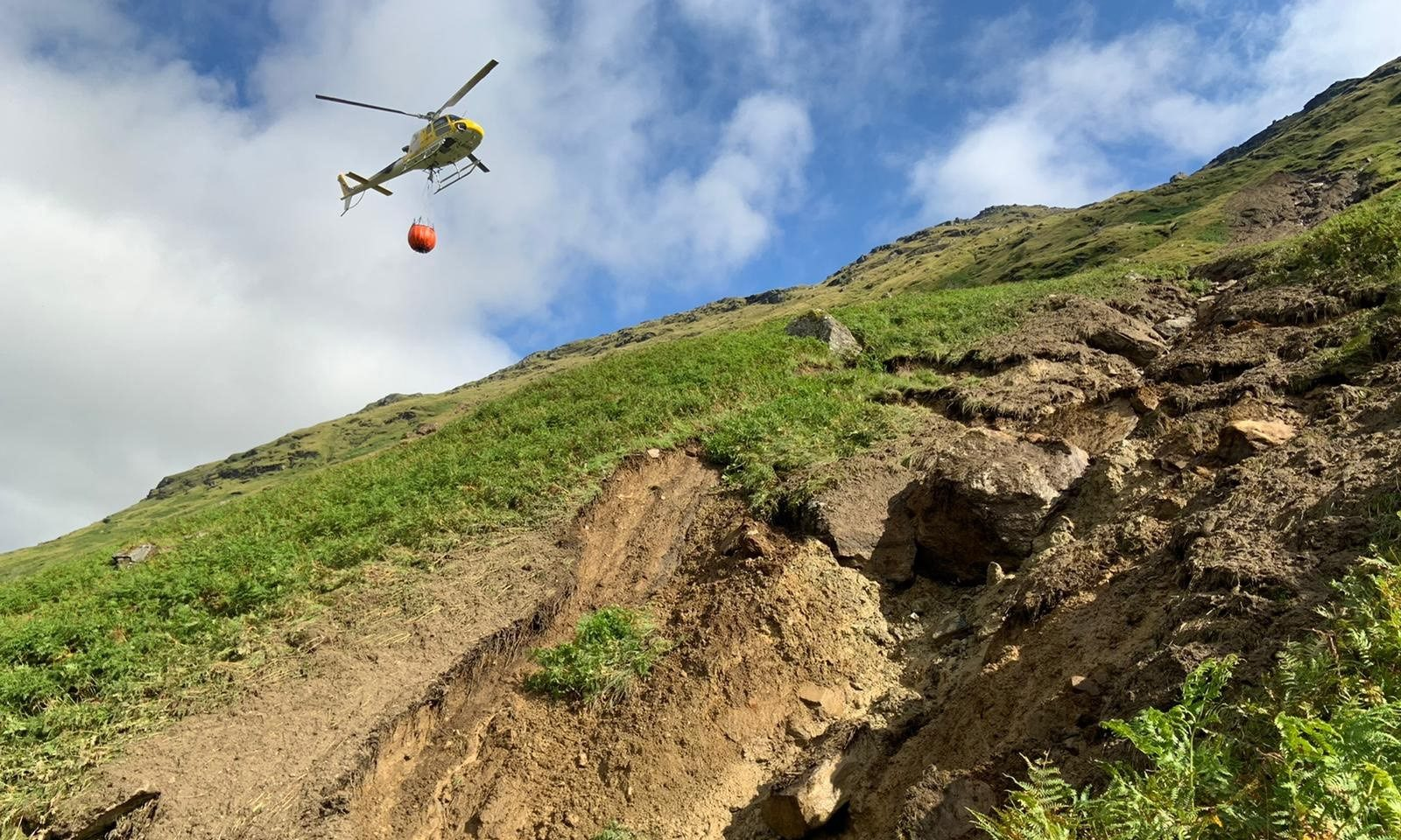The helicopter bringing water bags to site to help move large 100 tonne boulder to safety