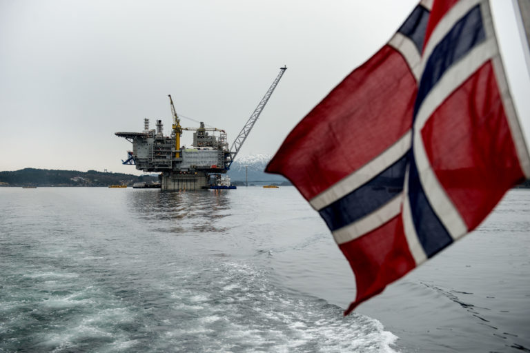 A Norwegian national flag flies from the back of a boat in view of the the Aasta Hansteen gas platform.