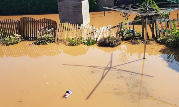 A shoe floats through the back garden of a property on Salmon Lane. At one point it was under three feet of water.