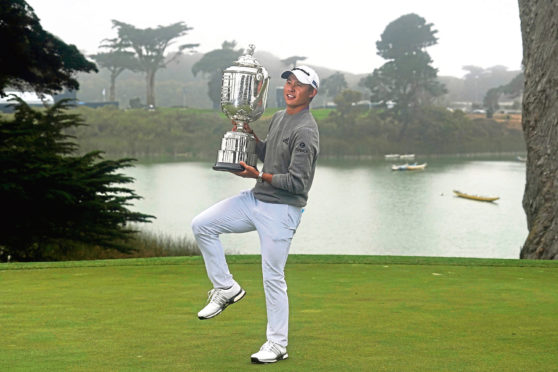 Collin Morikawa holds the Wanamaker Trophy