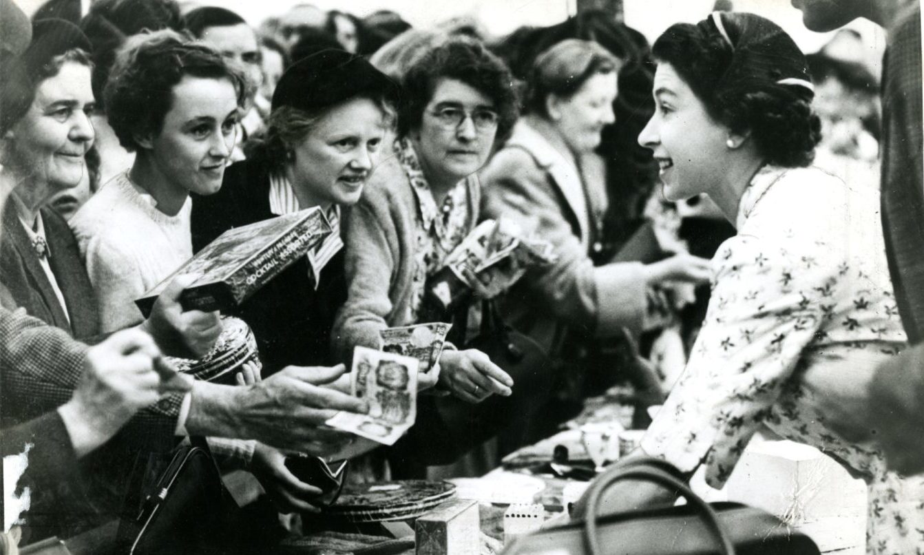 Queen Elizabeth hard at work at the memorable sale of work on Royal Deeside, 65 years ago.