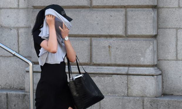 Amy Walker covered her face as she left Aberdeen Sheriff Court.