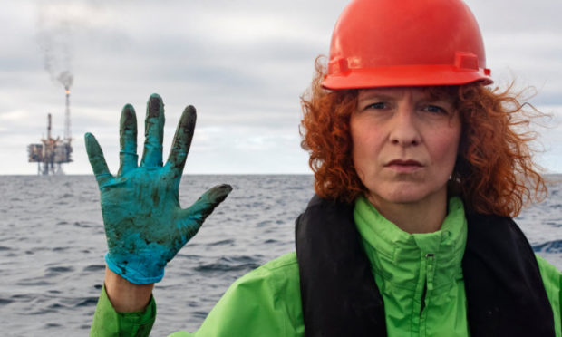 Greenpeace Germany Oceans campaigner Sandra Schoettner shows her gloves with the Andrew platform in the background