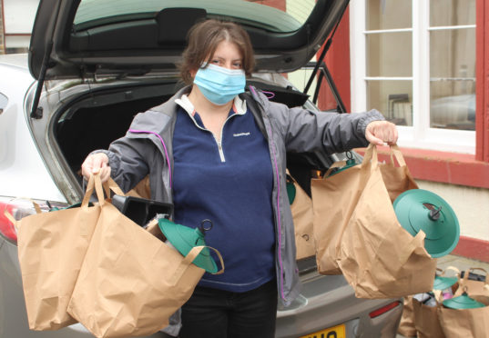 Maysie Calder of Sinclair's Bay Community Council taking a delivery of Green Health Packs.