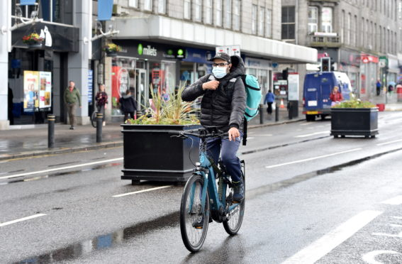 A Deliveroo delivery person cycling on Union Street, Aberdeen during the coronavirus outbreak. Picture by Darrell Benns.