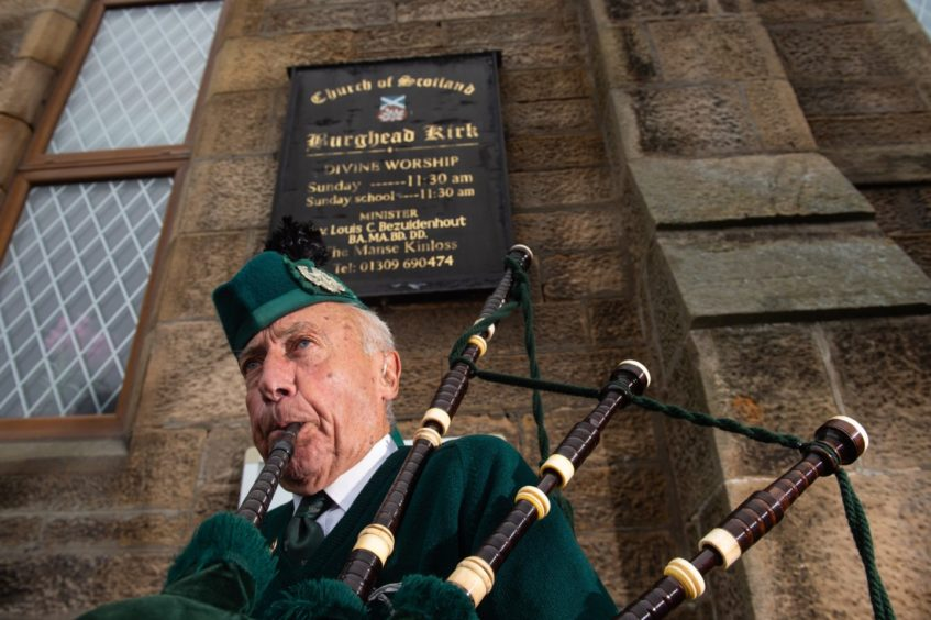 Beadle Piper Patrick Glendinning pipes outside Burghead's Church of Scotland in tribute to Christopher Stuchbury. Pictures by JASON HEDGES