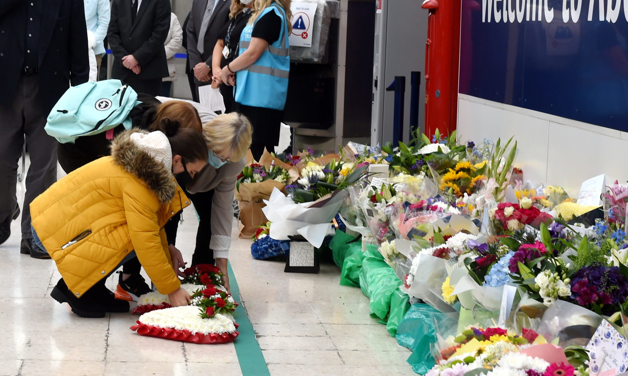 Family members laying wreaths and floral tributes at Aberdeen station.   Picture by Kenny Elrick