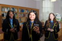 St Margaret's School For Girls pupils (left to right) Oluwatofunmi Adenuga, Janani Mohan and Caitlin O'Byrne looking over their results in the school library. Picture by Scott Baxter.
