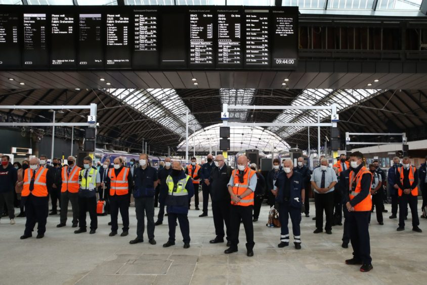 Members of the public join rail staff in Glasgow Queen Street station