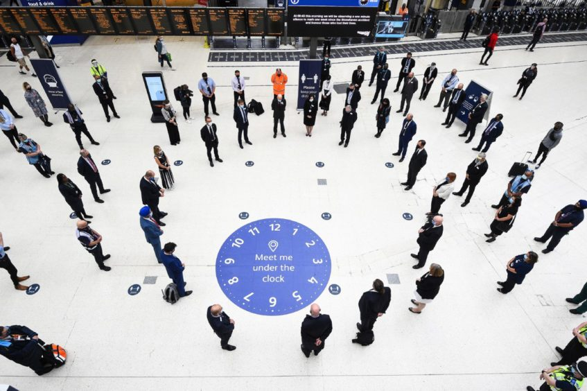 Rail staff stand in Waterloo station in London.