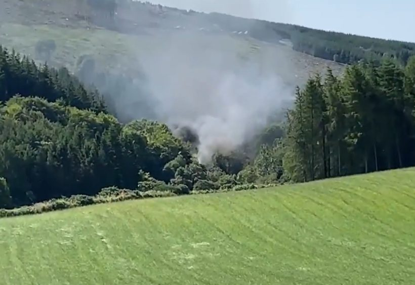 Screengrab from BBC Scotland showing smoke billowing from the train on the track in the countryside near Stonehaven, Aberdeenshire.
