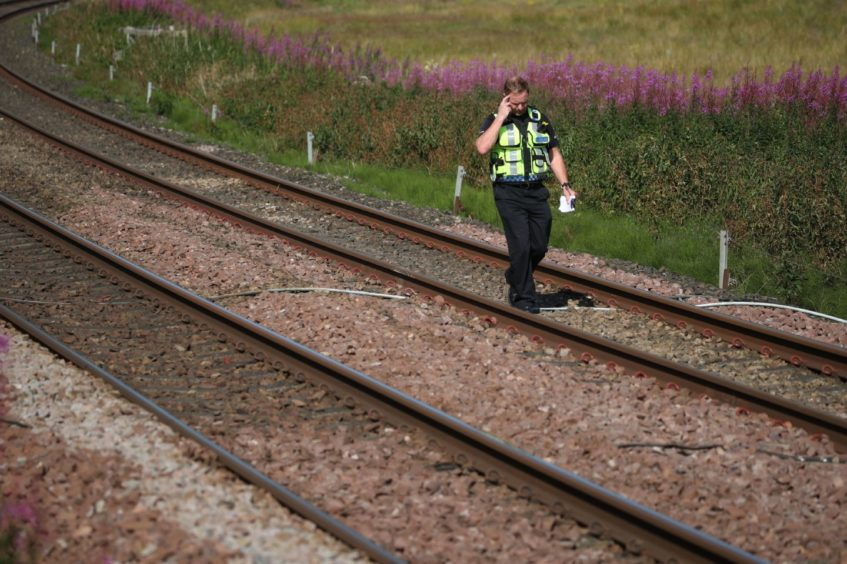 A police officer walks along the tracks at Carmont crossing.