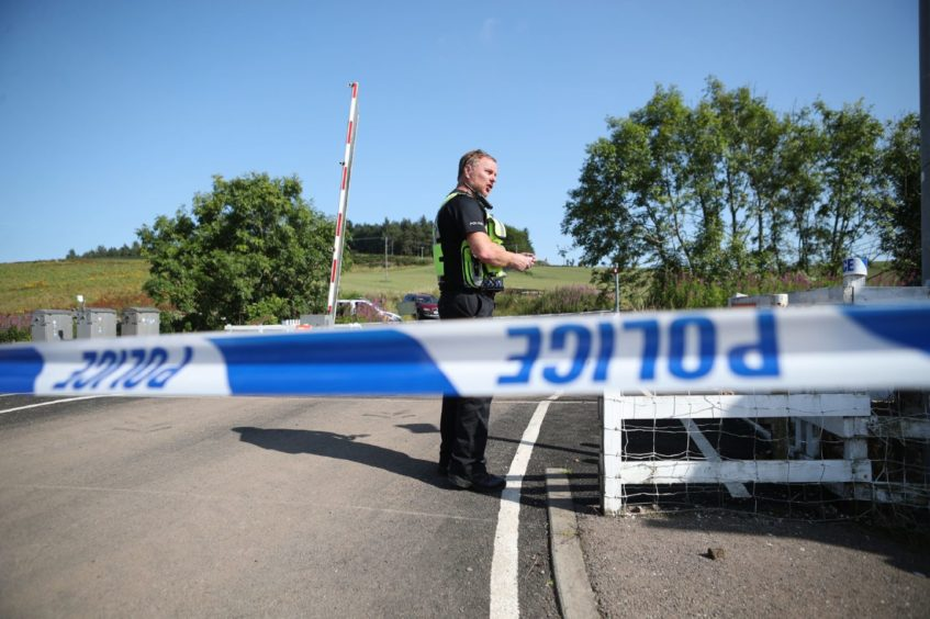 A police officer at a cordon at Carmont crossing, south of the scene in Stonehaven.