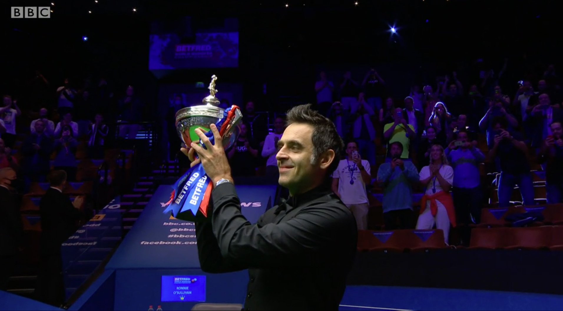 Ronnie O'Sullivan lifting the Betfred World Snooker Championship trophy.