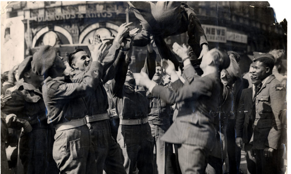 Soldiers celebrating Victory over Japan in Piccadilly Circus, London.