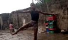 Anthony Madu pictured dancing in the rain with no shoes.