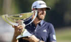Dustin Johnson holds up the FedEx Cup trophy after winning the Tour Championship golf tournament