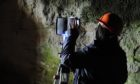 Archaeologists conducting Terrestrial Laser Scanning at the Sculptor's Cave in Moray.
