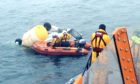 RNLI and coastguard volunteers inspecting the wreckage