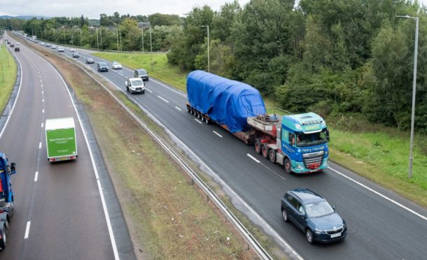 The locomotive being transported with a police escort on the A90.
