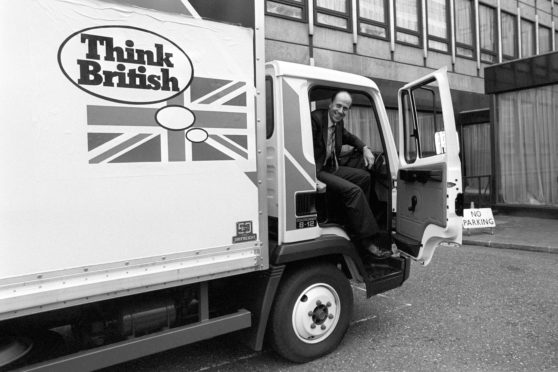 Norman Tebbit ready to step from the Leyland Roadrunner after parking it following his 'test' drive in London when it was launched.