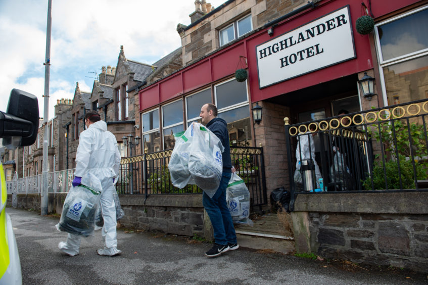 Police load a van outside the Highlander Hotel in Buckie.