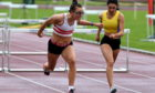 Jane Davidson, left, and Briagha Cook cross the line in the 100-metre hurdles at Aberdeen Sports Village.  Picture by Kenny Elrick