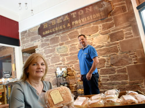 Owner Ann MacKinnon with her partner David Shields and the old shop sign they discovered. Picture by Sandy McCook.